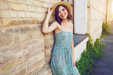 Sunny lifestyle fashion portrait of young stylish hipster woman wearing straw hat.