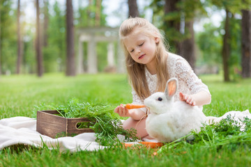 Little girl playing with white rabbit outdoor
