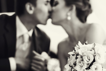 Wedding bouquet lies on the frontground of a black and white pic