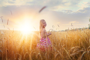 Little girl on a wheat field with her arms outstretched in the sunset.