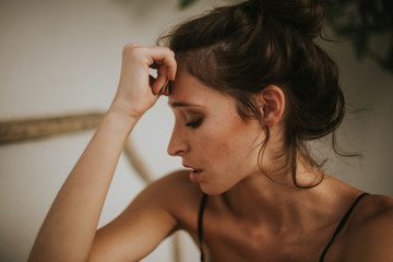 Close-up of brunette with hair in bun looking down