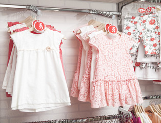 Children fashion clothing on hangers at the show