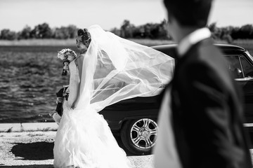 Wind blows bride's veil while she stands behind an old car