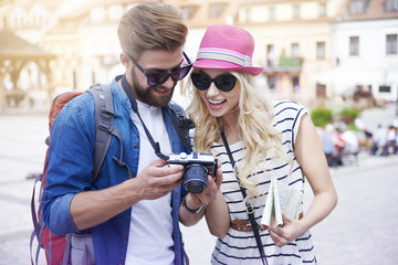 Happy couple looking on pictures from vacation