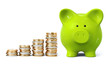 Green piggy bank with coin stacks in ascending order