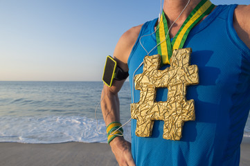 Hashtag gold medal athlete wearing mobile phone armband stands listening to motivational music at sunrise on Ipanema Beach in Rio de Janeiro, Brazil