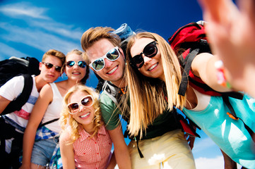 Teenagers with backpacks taking selfie, summer festival