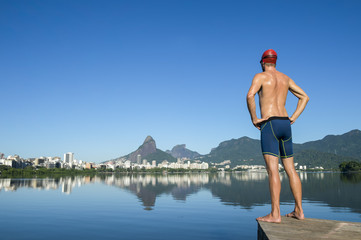 Athlete swimmer with swimming cap standing in front of the Rio de Janeiro skyline at Lagoa Rodrigo de Freitas lagoon