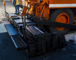 close-up details of industrial machinery working with asphalt, mixing bitumen with hot asphalt, layering on the road surface