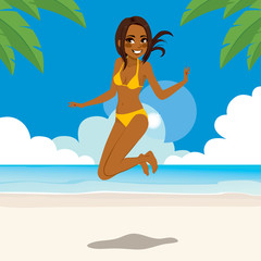 African American woman in bikini jumping happy on tropical beach