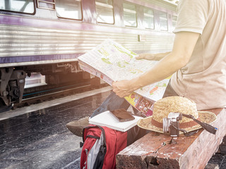 Traveler sitting and looking at the map in train station. Travel concept