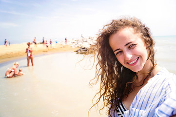 Beautiful woman on beach, smiling, taking selfie, sunny day