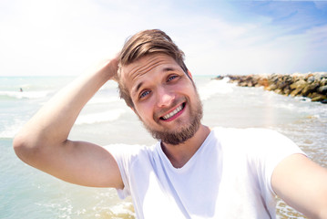 Hipster man on beach, smiling, taking selfie, sunny summer