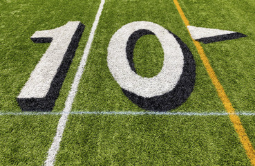 Ten yard line with white lettering on an American football field.