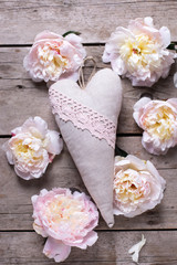 Decorative heart and  pink peonies flowers on aged wooden background. Flat lay.  Selective focus.