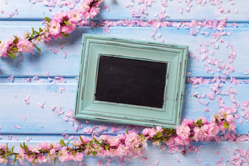 Pink flowers  and empty blackboard on blue wooden planks.