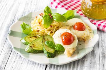 Italian lunch: chicken with mozzarella ,spaghetti and zucchini