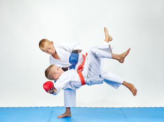 Children are training throws on a blue mats