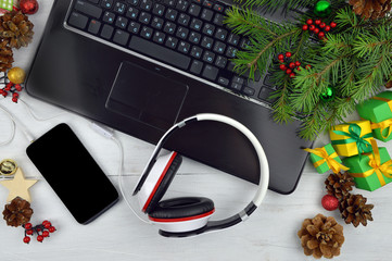 Christmas melodies.Smartphone and headphones on a wooden backgro