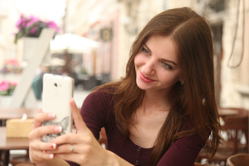Happy woman making selfie photo on smartphone