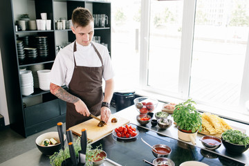 Young man with tattooed arm in apron cooking in kitchen