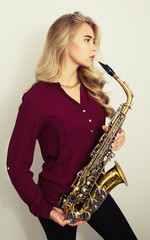 Profile of beautiful young woman holding saxophone.