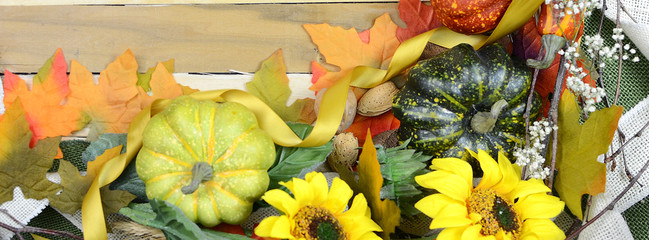 Cheerful fall or autumn border with fall leaves, nuts, sunflowers and squashes with green folded burlap and gold ribbon on a wooden background. Sized for social media banner