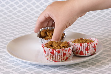 Hand placing paleo pumpkin muffins onto a plate.