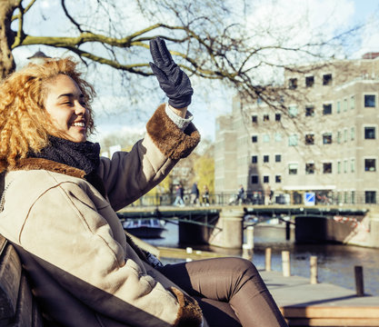 cute pretty mulatto woman waving and smiling welcoming friends, streets of Amsterdam