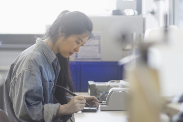 Female technician soldering electronic components in an industrial plant, Freiburg Im Breisgau, Baden-württemberg, Germany