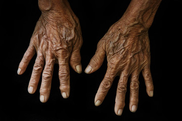 Old hands on a black background