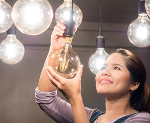 asian woman changing light bulb