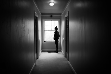 Young woman in a dark hallway looking out a window.