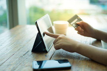 Shopping through tablet and pay by credit card.