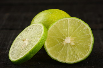 Slices of organic lime in dark background,