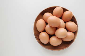 Eggs in wooden bowl on white copy space background