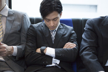 Young business man sleeping on a train