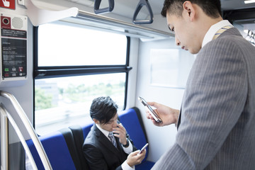 Business people are crazy about the smartphone game on a train