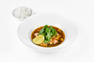 Crab with chili sauce, lime, parsley and rice on a plate on a white background