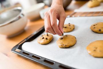 Woman adding chocolate chip cookies