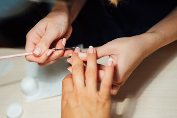 Woman in salon receiving manicure