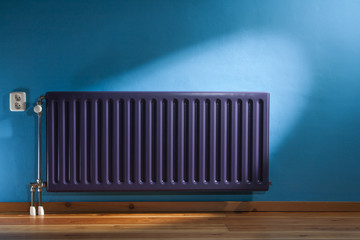 Purple radiator and a blue wall