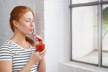 frau steht am fenster und trinkt tomatensaft
