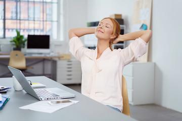 zufriedene frau im büro streckt den rücken und lächelt