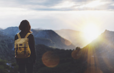 Hipster young girl with backpack enjoying sunset on peak of foggy mountain. Tourist traveler on background view mockup. Hiker looking sunlight flare in trip Spain. Picos de Europa. Journey concept Wall mural