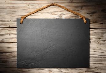 black slate signboard on aged wall