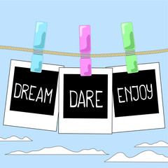 Rope with photo frames on cloudy sky background. Motivation words Dream, Dare, Enjoy on instant photos.