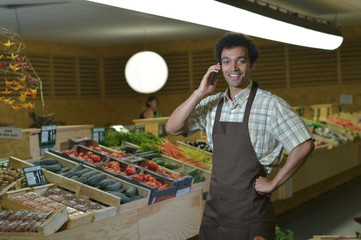 Grocery clerk phoning in produce aisle of supermarket store