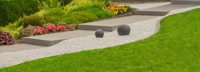 Spoed Foto op Canvas Tuin Moderner Steingarten mit Außentreppe, Felsen, Ziersplitt und Steinkugeln im Panoramaformat - Modern rock garden with outside stairs , rocks , decorative gravel and stone balls in panoramic format