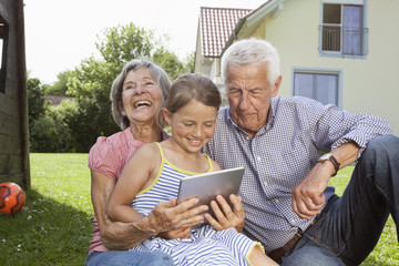 Grandparents and granddaughter in garden using digital tablet